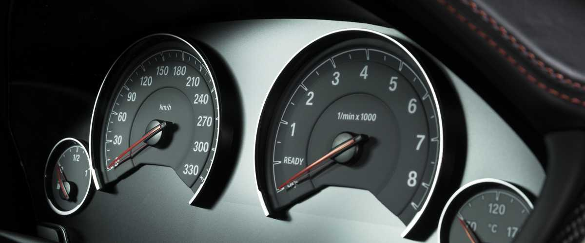 Car dashboard looking at the speedometer