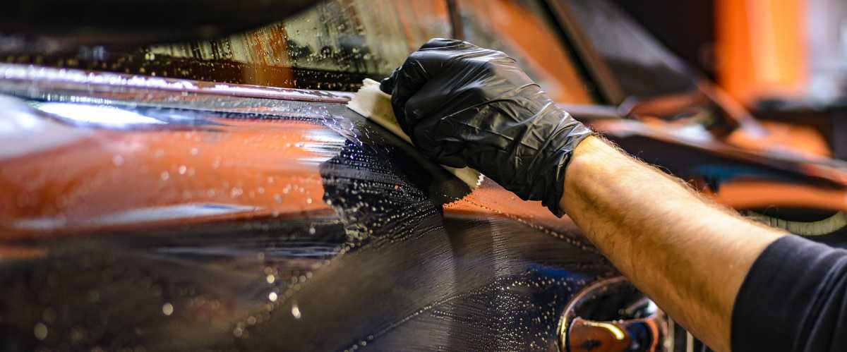 Wet car being scrubbed by a worker